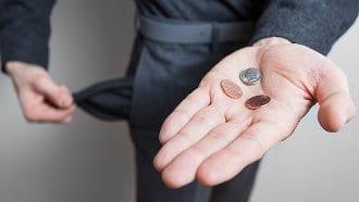 Mężczyzna trzyma na dłoni monety, które wyjął z kieszeni