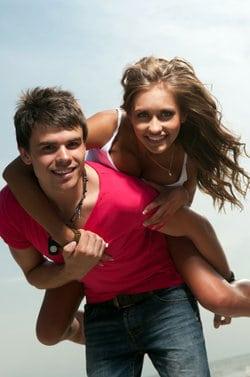 Młody chłopak trzyma na barana swoją dziewczynę, która go obejmuje