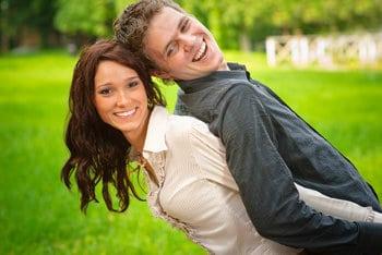 Uśmiechnięta młoda kobieta trzyma opartego o jej plecy młodego mężczyznę