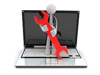 Na laptopie stoi ludzik z kluczem metalowym do wkręcania śrub