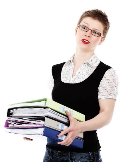 Kobieta z biura niesie trzy wypełnione dokumentami segregatory