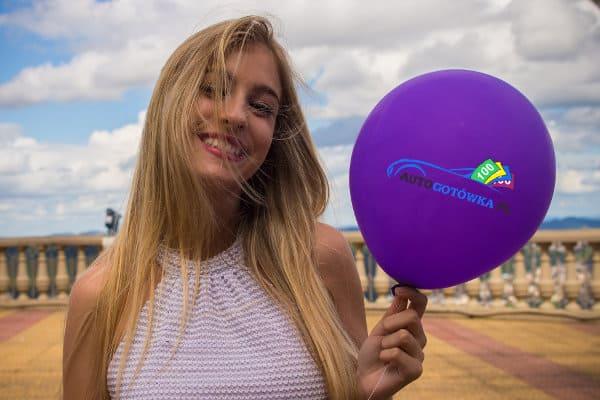 Kobieta trzyma fioletowego balona z napisem Autogotówka