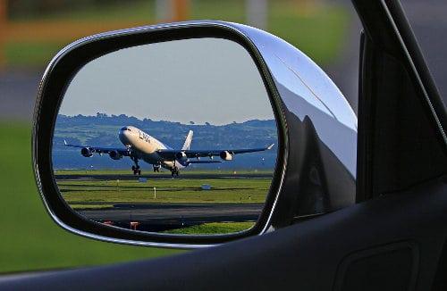 Lusterko samochodu, w którym widać samolot