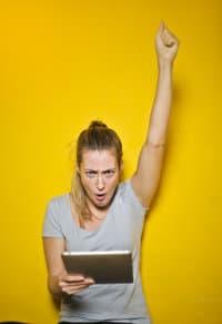 Kobieta trzyma tablet i unosi do góry rękę