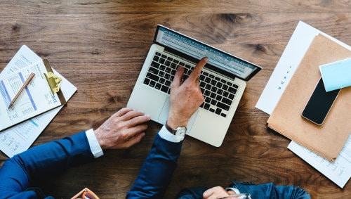 Mężczyźni w firmie rozmawiają przy laptopie