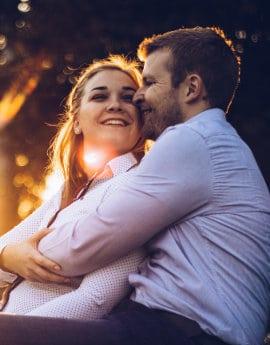 Uśmięchnięta kobieta i mężczyzna przytulają się do siebie