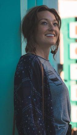 Uśmiechnięta kobieta oparta o ścianę