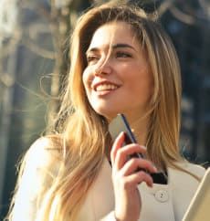 Blondynka trzyma w dłoni telefon komórkowy