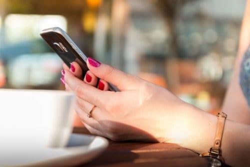 Kobieta trzyma w dłoniach smartphone