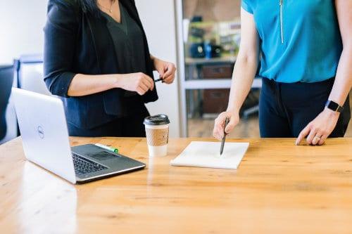 Dwie kobiety stoją przy biurku z laptopem